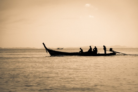 Silhouettes of fishermen in the boat and beautiful abstract landscape in Phi Phi Island - Thailand. photo