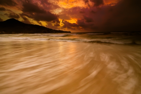 Colorful sunset with stormy sky and golden beach in Phuket - Thailand.