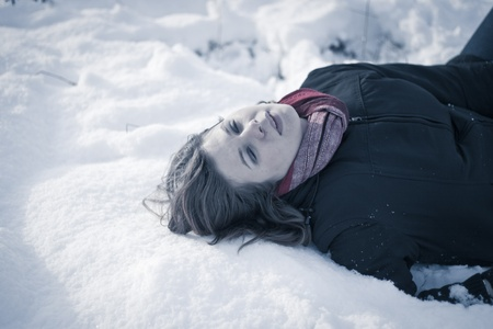 Frozen to death concept. Young female model lying on snow. photo