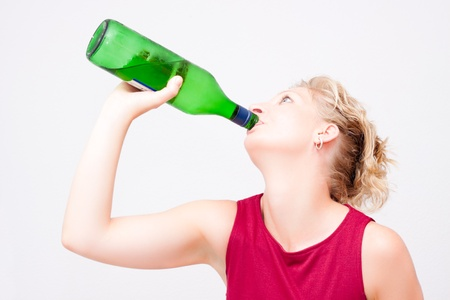 Young woman with bottle of alcohol, isolated on white background. photo