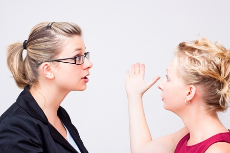 to argue: Two young business women conflict. Stock Photo