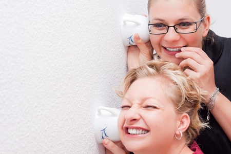 Funny moment of two young women spying. Stock Photo