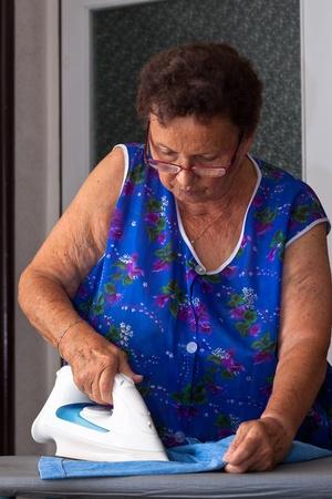 Portrait of senior woman ironing clothes.