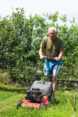 Portrait of elderly man mowing lawn in the garden. Stock Photo - 10916634