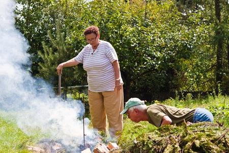 Senior couple trying to make a bonfire in the garden. photo