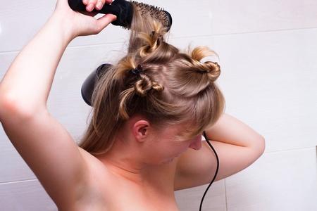 Detail of young woman taking care of hair. photo