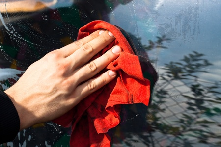Man's hand with red rag washing car window.