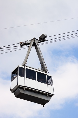cableway: Cable Car on wires over cloudy sky with non-recognisable silhouettes of people inside. Stock Photo