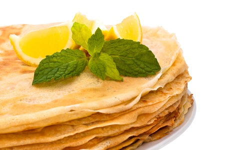 Stack of homemade crepes on the plate, isolated on white background. A crepe is a type of very thin pancake. It is very popular in France. Crêpe may contain a variety of fillings. It can serve as main meal or a dessert. Standard-Bild