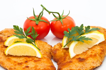 breaded: Detail of schnitzel with lemons and tomatoes, isolated on white background. Stock Photo