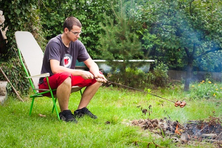 Young man grilling sausages on campfire. photo