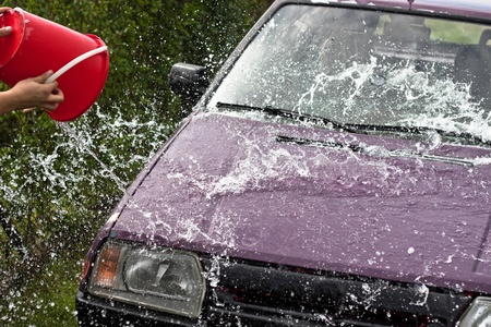 Quick car wash, pouring and spraying water from backet. photo