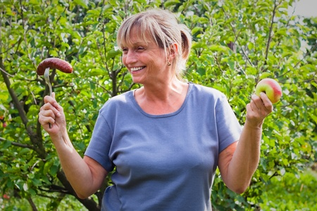 deciding: Portrait of middle aged woman holding sausage and apple. Healthy lifestyle and diet conceptual photo.