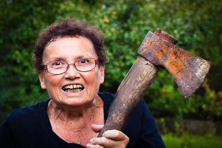狂気の年配の女性の持ち株斧。 写真素材