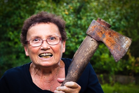 Crazy senior woman holding axe. photo