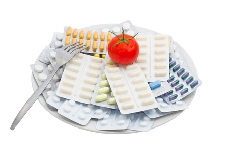 antibiotic: Pills and tablets with tomato on plate, isolated on white background.