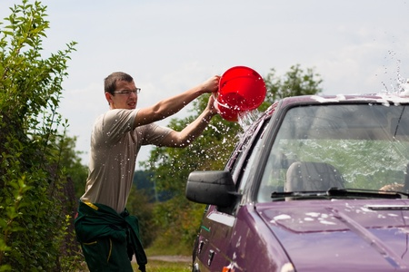 A young man washing car, pouring water from bucket. photo