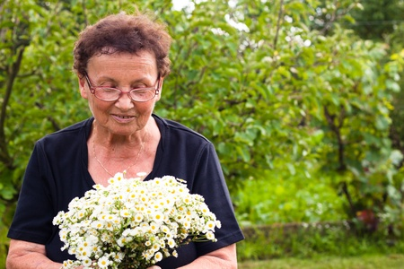 Senior woman with flowers in the garden. photo