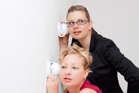 snoop: Funny moment of two young women listening through the wall. Stock Photo