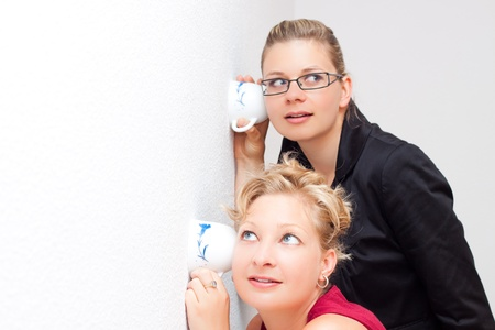 spy girl: Funny moment of two young surprised women listening through the wall. Stock Photo