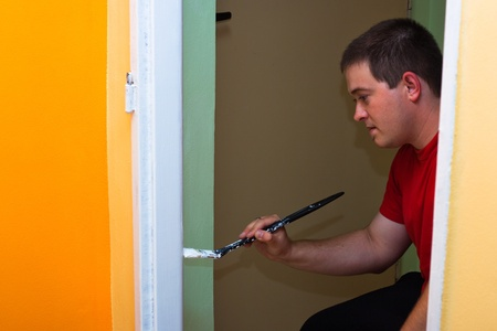 Young man painting new home. photo