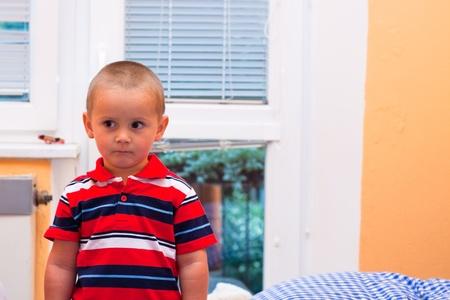 Portrait of frightened little boy indoors. photo