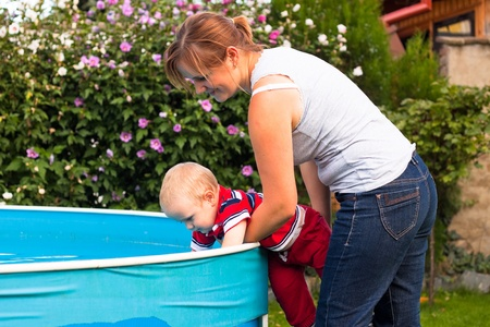 discovering: Young woman and toddler discovering swimming pool in the garden.