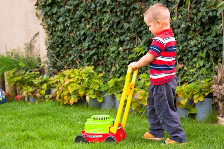 mow: Little boy gardening, playing with toy lawn mower.
