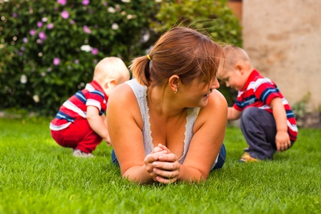 Portrait of happy mother with children enjoying garden. photo