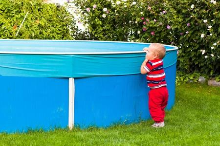 Toddler boy exploring swimming pool in the garden. photo
