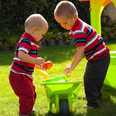 hermanos jugando: Los hermanos peque�os jugando en el jard�n.