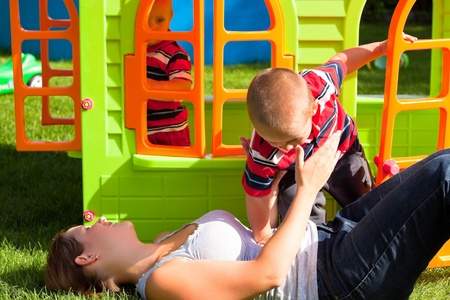 Happy family and colorful playhouse. Mother and two little boys having fun in the garden. photo