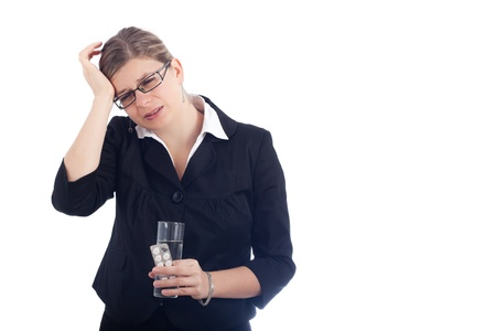 Unhappy young woman with headache holding glass with water and painkillers. Isolated on white background. photo