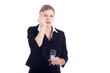 Portrait de jeune femme avec les maux de dents, tenant le verre avec de l'eau et des comprimés. Isolé sur fond blanc. Banque d'images