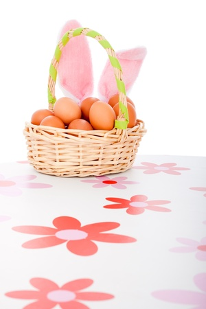 Easter basket with eggs and bunny ears, isolated on white background. photo