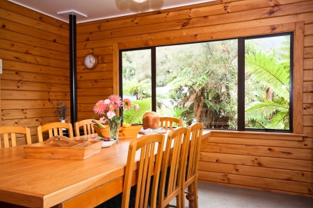 Nice warm interior of mountain wooden lodge dining room. Fox Glacier Lodge, Fox Glacier, West Coast, South Island, New Zealand.