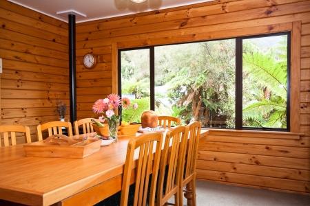 Nice warm interior of mountain wooden lodge dining room. Fox Glacier Lodge, Fox Glacier, West Coast, South Island, New Zealand. Stock Photo