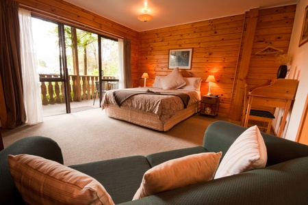 hotel suite: Nice warm interior of mountain wooden lodge bedroom. Fox Glacier Lodge, Fox Glacier, West Coast, South Island, New Zealand. Stock Photo