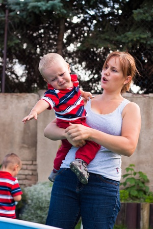 Young mother holding grumpy crying toddler boy outdoors in the garden. Stockfoto