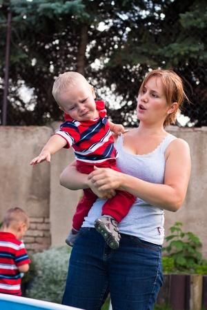 grumpy: Jonge moeder met chagrijnig huilende peuter jongen buiten in de tuin.