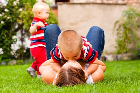 mom kiss son: Happy mother kissing her son relaxing on the grass in the garden. Stock Photo