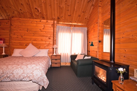 fox glacier: Lodge bedroom interior with fireplace. Fox Glacier Lodge, Fox Glacier, West Coast, South Island, New Zealand.