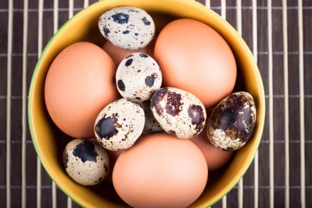 huevos de codorniz: Primer plano de un tazón con los huevos de pollo y huevos de codorniz sobre fondo de rayas marrón. Foto de archivo