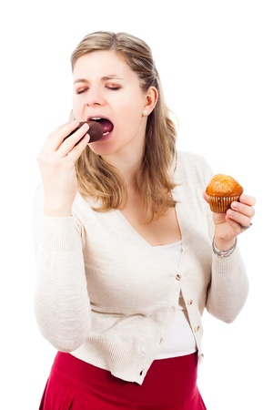 Young woman enjoying eating delicious chocolate donut and sweet muffin, isolated on white background.