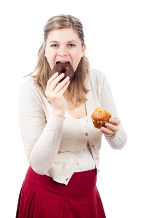 woman eating cake: Young woman eating delicious chocolate donut and sweet muffin, isolated on white background.