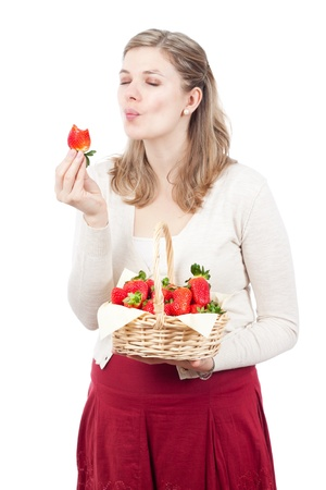 Beautiful young woman enjoying fresh strawberries, isolated on white background. photo