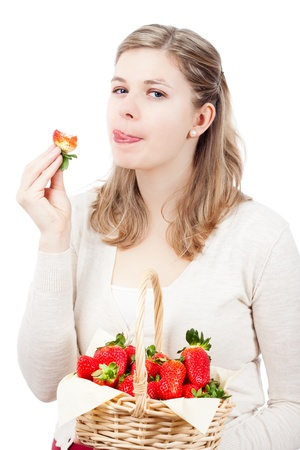 Beautiful young woman eating fresh strawberries, isolated on white background. photo