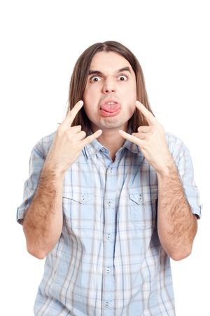 sacar la lengua: Joven hombre de pelo largo groseros gestos y sacar la lengua, aisladas sobre fondo blanco. Foto de archivo
