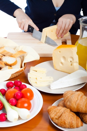 Detail of kitchen table with fresh food and female hands cutting emmenthal cheese. photo