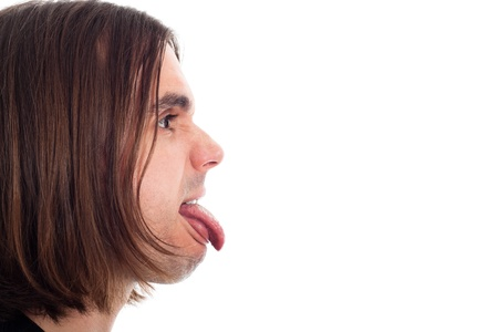 making a face: Profile of young long haired man face sticking out tongue, isolated on white background with large copy space.